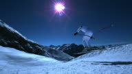 Steady shot of skier jumping downhill by night.
