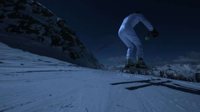 Steady shot of skier jumping downhill.