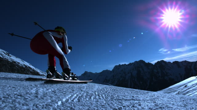 Steady shot of skier passing camera and skiing downhill.