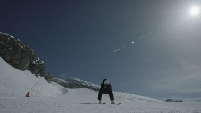 Steady shot of skier skiing downhill straight towards the camera.