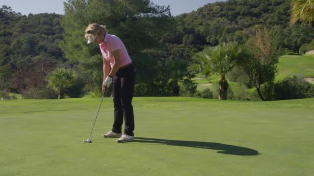 MS TS (steadycam) mature woman golfer on putting green hitting ball, camera tracks ball along grass RED R3D 4K