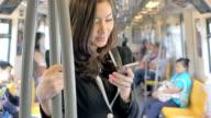 Steadycam shot of Businesswoman using smartphone on train,Close-up