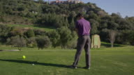 TS DS (steadycam) young golfer standing on tee, doing one practice swing and then teeing off; camera tracks around him and has tee-off from rear view RED R3D 4K