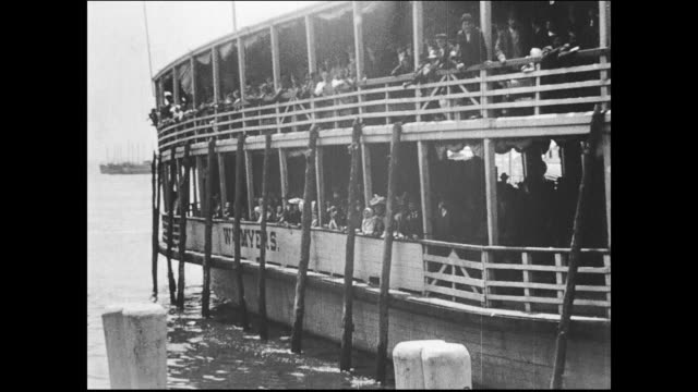steam ferryboat 'William Myers' approaches dock at Ellis Island Immigration Station many passengers on board / immigrants disembark the gangway and...
