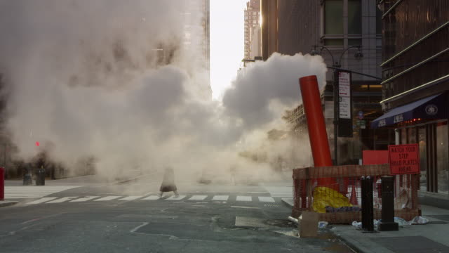 A steam pipe pushes steam out on a empty street in New York City on Madison and 46th Streets.