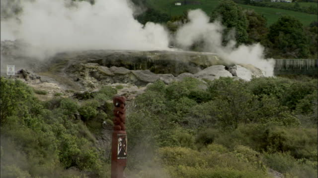 Steam pours out of rocks and surrounds a maori totem. Available in HD.