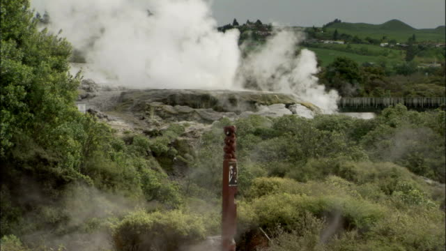 Steam pours out of rocks at a geothermal area. Available in HD.