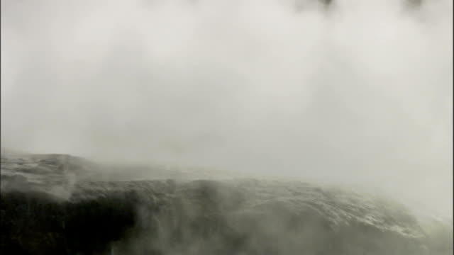 Steam pours out of rocks next to a geothermal pool. Available in HD.