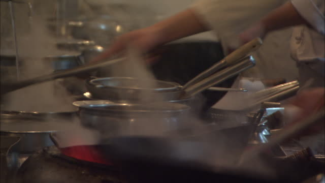 Steam rises as a restaurant cook ladles hot water into a wok and scrubs the pan over an open flame.
