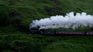 A steam train chugs across the Glenfinnan Viaduct near Argyll, Scotland. Available in HD.