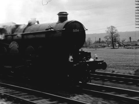 A steam train moves along a railway line