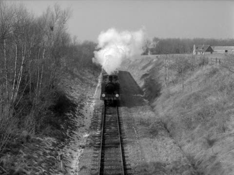 A steam train moves along a track in the countryside and passes underneath the camera