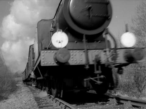 A steam train passes the camera on a railway line in the countryside