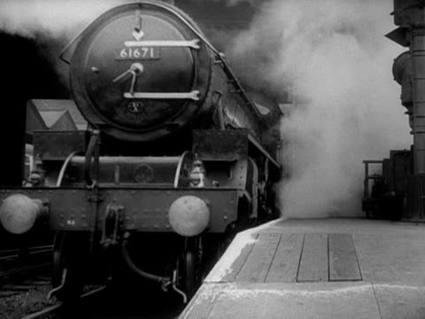 A steam train pulls out of a train station