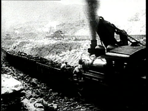 Steam trains pushes cars full of dirt during the construction of the Panama Canal