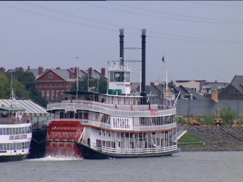 Steamboat moored on Mississippi river as paddle rotates