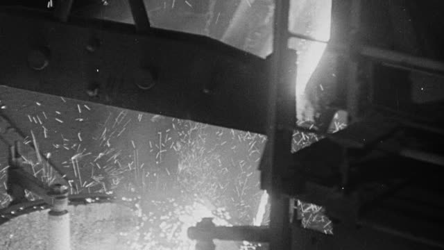 1948 MONTAGE Steel being heated, moved by cranes, and molded by steel workers in a mill / Sheffield, England, United Kingdom