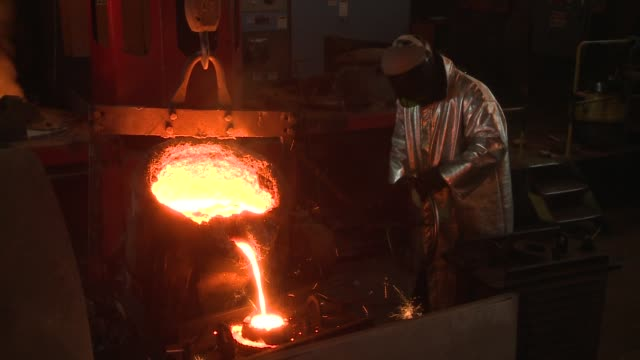 A steel worker in a fire-resistant suit stands near a pulley and pours molten steel into a cylinder. Available in HD.