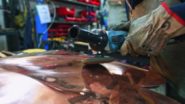 Steel worker polishing metal surface in workshop