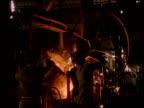 Steel worker removes molten steel from furnace Calcutta.