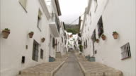 A steep alley runs between white apartment buildings in the village of Mijas, Spain.