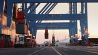Stevedores Manoeuvring Shipping Containers at Port