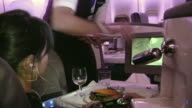 CU, Stewardess serving dinner to woman in First Class of plane