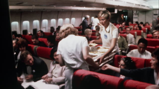 Stewardesses serve trays of food to hungry airline passengers.