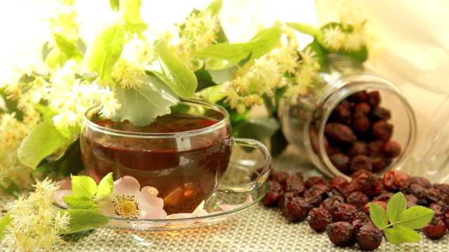 still life of tea with linden flowers and rosehips