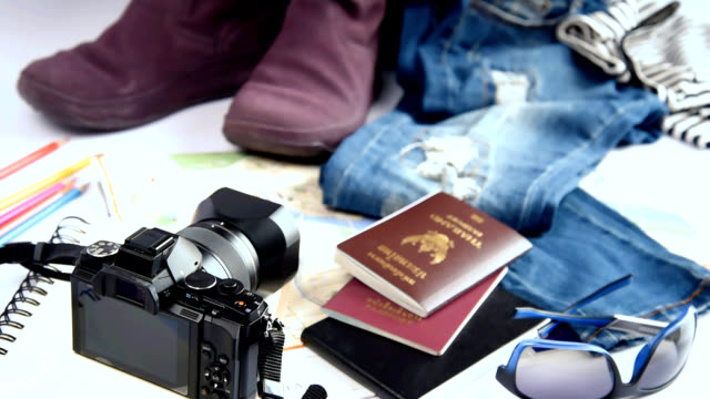 Still life of travelling concept with camera, jean, boots, handbag on white background