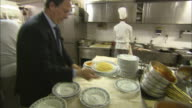 Still shot of a restaurant owner and chefs in the kitchen