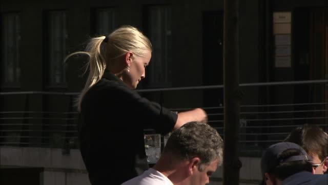 Still shot of a waitress taking an order outside