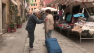 Still shot of an older woman greeting someone