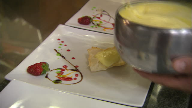 Still shot of desserts being plated at Italian restaurant