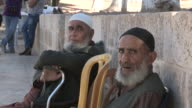 Still shot of two old Muslim men sitting next to a low wall NO