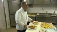 Still shot of waiters and chefs talking in the kitchen