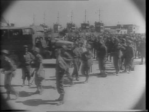 Still shots of blimps in the air / shots of American Fifth Army in Africa in uniform at their staging area / soldiers boarding boats carrying bags /...