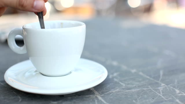 Stirring a cup of fresh coffee on a marble cafe table, outdoors