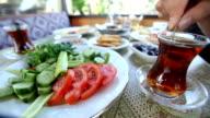 stirring Turkish tea at Turkish breakfast