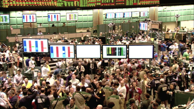 Stock brokers crowd an exchange floor. Available in HD.