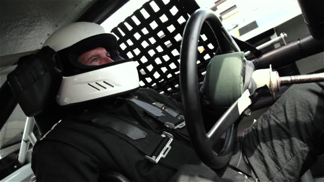 Stock-car driver grips and turns steering wheel, shifts gears