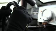 Stock-car driver's hands grip steering wheel, shift gears