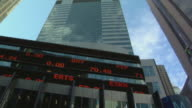 T/L LA WS Stock market data scrolling across stock ticker board on office building / New York, New York, USA