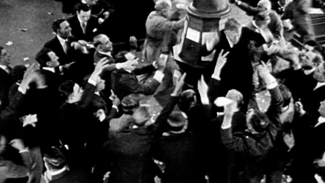 Stock market traders crowding around market maker in the stock trading pit of the New York Stock Exchange reenacting the 1929 stock market crash