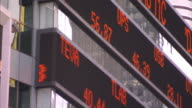 Stock prices scroll across an electronic stock ticker on a building in New York City.