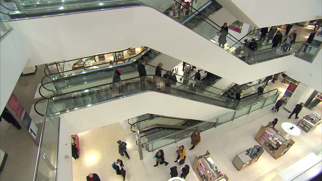 Stock shots of shopping mall interiors escalator showing people going up and down escalator inside Marks Spencer Pantheon Oxford Street