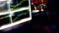 Stockbroker monitoring stock market charts in LED display.