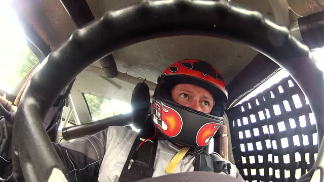 Stock-car driver shifts gears, checks rearview mirror (Steering-Wheel POV)