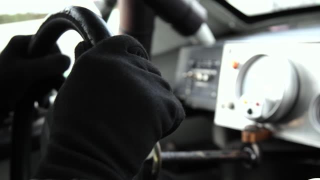 Stock-car driver's hands grip steering wheel, shift gears