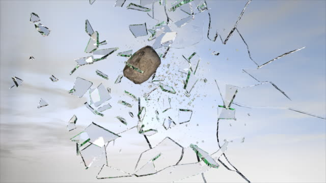 stone breaking glass during the day slow motion